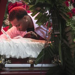 """Anthony Sanders hugs his grandmother, Bettie Jones, who was """"accidentally"""" shot to death by a Chicago Police officer the day after Christmas, during her funeral at New Mount Pilgrim Missionary Baptist Church on Wednesday, Jan. 6, 2016."""