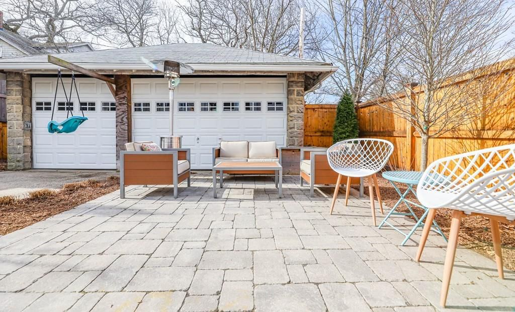 A large brick patio with furniture in front of garage.