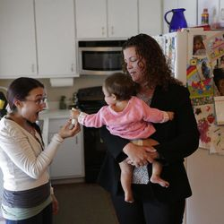In this Sept. 26, 2012 picture, Sabina Widmann, right, holds her baby girl Stella while domestic worker Alicia Wotherspoon, left, holds a bannana before work at their home in San Diego.
