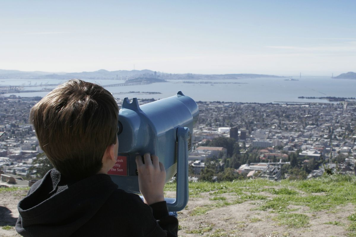 A small child looking through binoculars toward the East Bay.