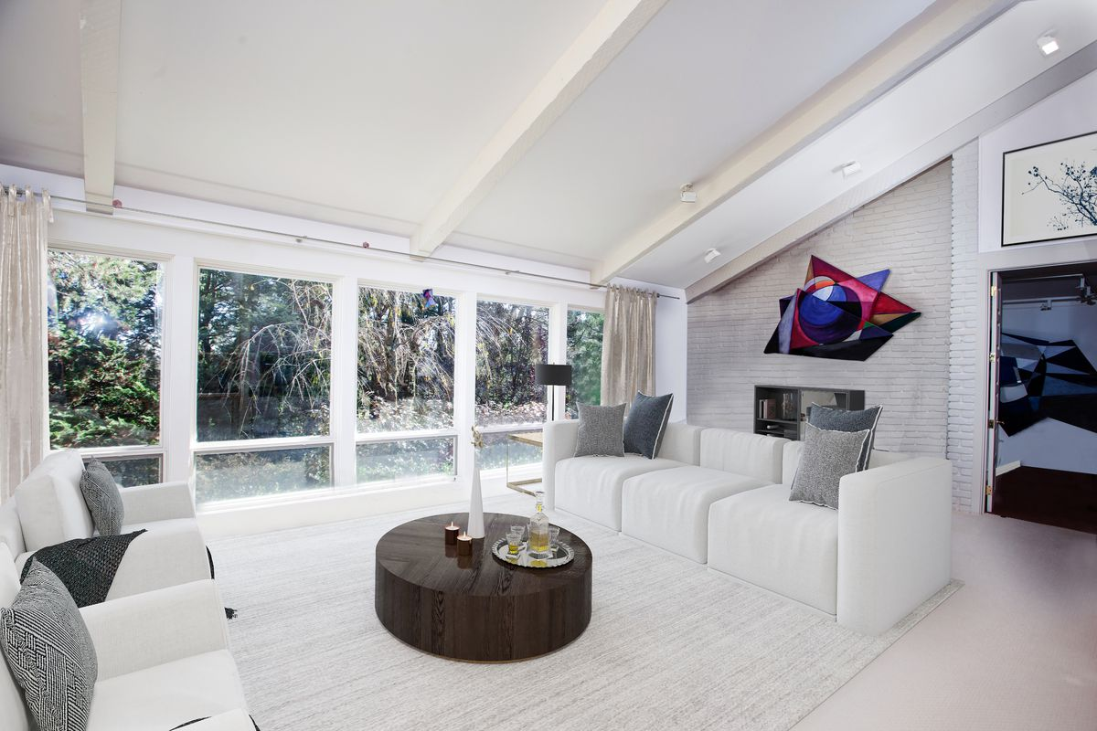 A living room has two white couches, a round solid coffee table, and a vaulted ceiling with windows on one side.