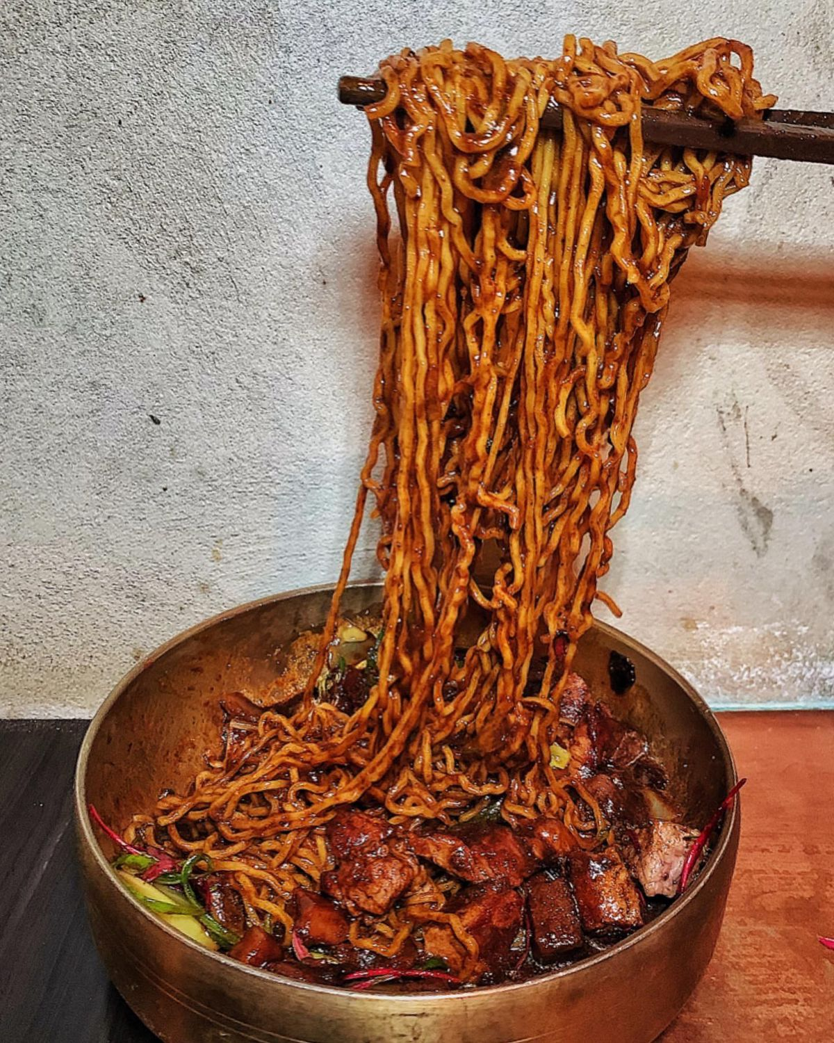 A metal bowl with noodles and steak inside, with noodles being pulled up.