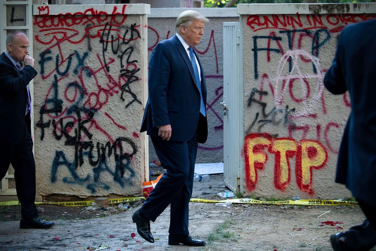 Donald Trump walking past graffitied concrete walls.