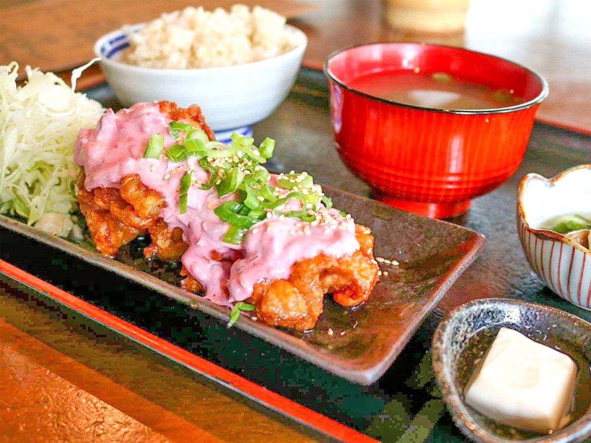 Fried chicken topped with bright pink tartar sauce beside shredded cabbage, on a tray with rice, soup, and pickles