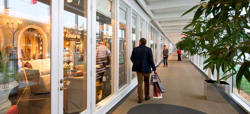 A person holding several shopping bags looks into the window of a furniture store. Inside the furniture store are many design and furniture objects.