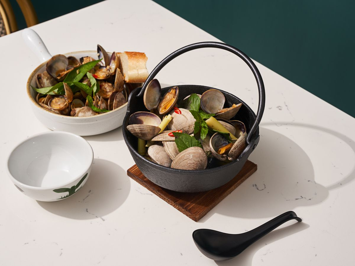 Three dishes sit on a white table, two of which are filled with clams topped in herbs and sauce