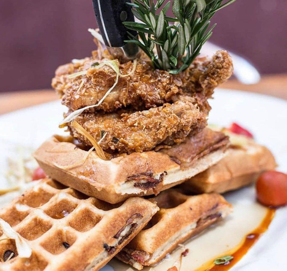 Plate containing waffle topped with fried chicken and herbs
