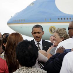 President Barack Obama greets people on the tarmac as he steps off of Air Force One as he arrives at at Buckley Air Force Base, Tuesday, April 24, 2012, in Aurora, Colo.
