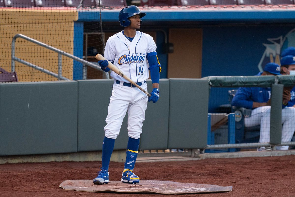 """A baseball player in white pants and a white top that reads """"Storm Chasers #14"""" stands in the on-deck circle near a dugout, holding a bat near his waist and looking pensively off to the right."""