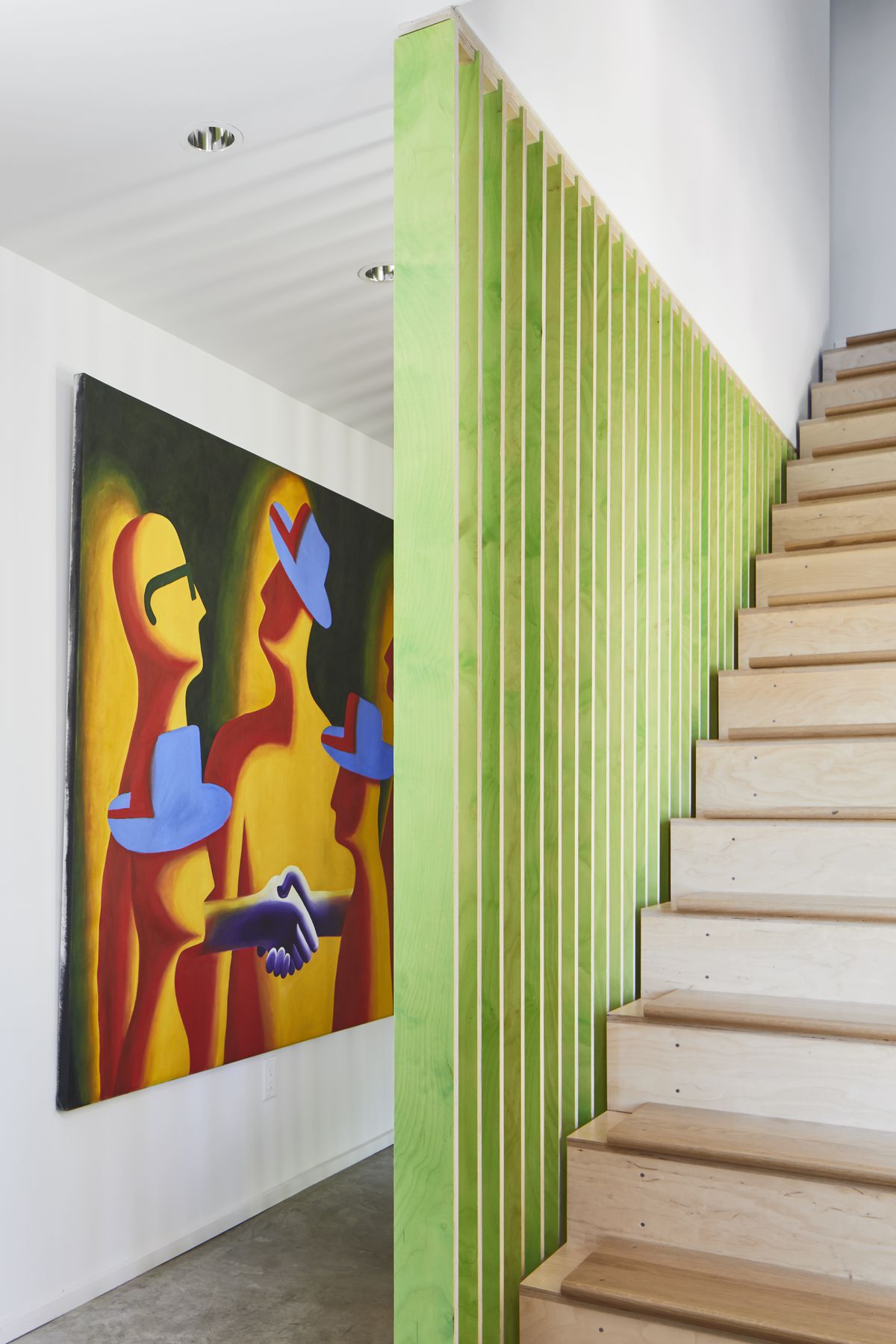 A staircase with wooden stairs. There are green wooden slats on the side of the stairs. There is a colorful work of art hanging on a white wall facing the staircase.