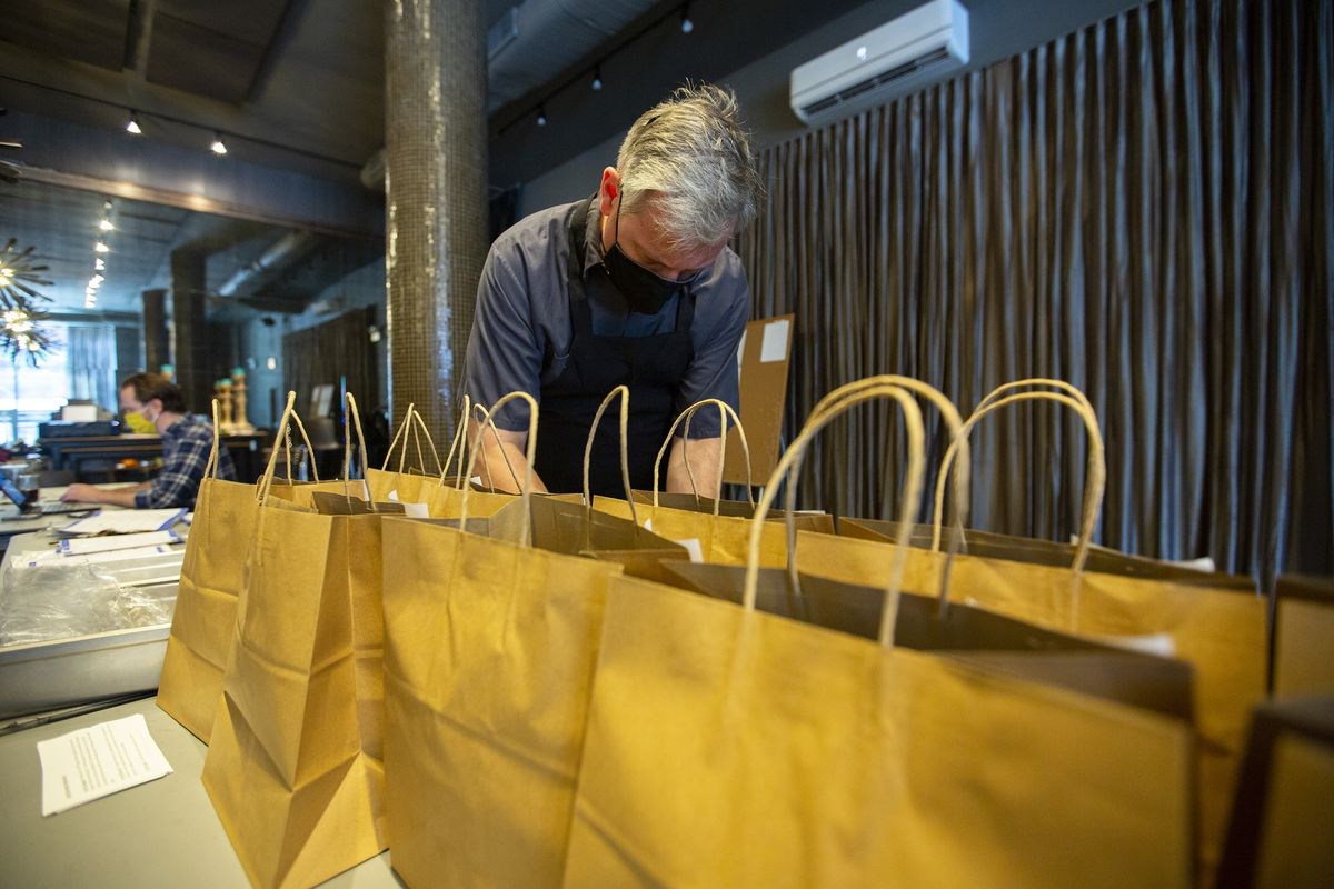 A white chef leans over two rows of brown bags.