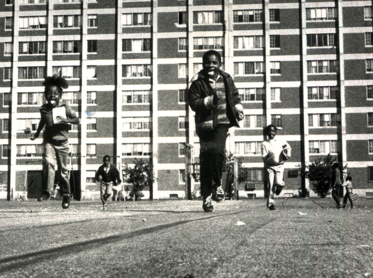 """3-13-2002 Copy photo of Cabrini Green on September 23, of children running along the Cabrini Green campus six months after then Mayor Jane Byrne occupied an apartment in """"Cabrini Green"""". This photo was part of a Pulitzer Prize winning portfolio by John H. White, Chicago Sun-Times"""