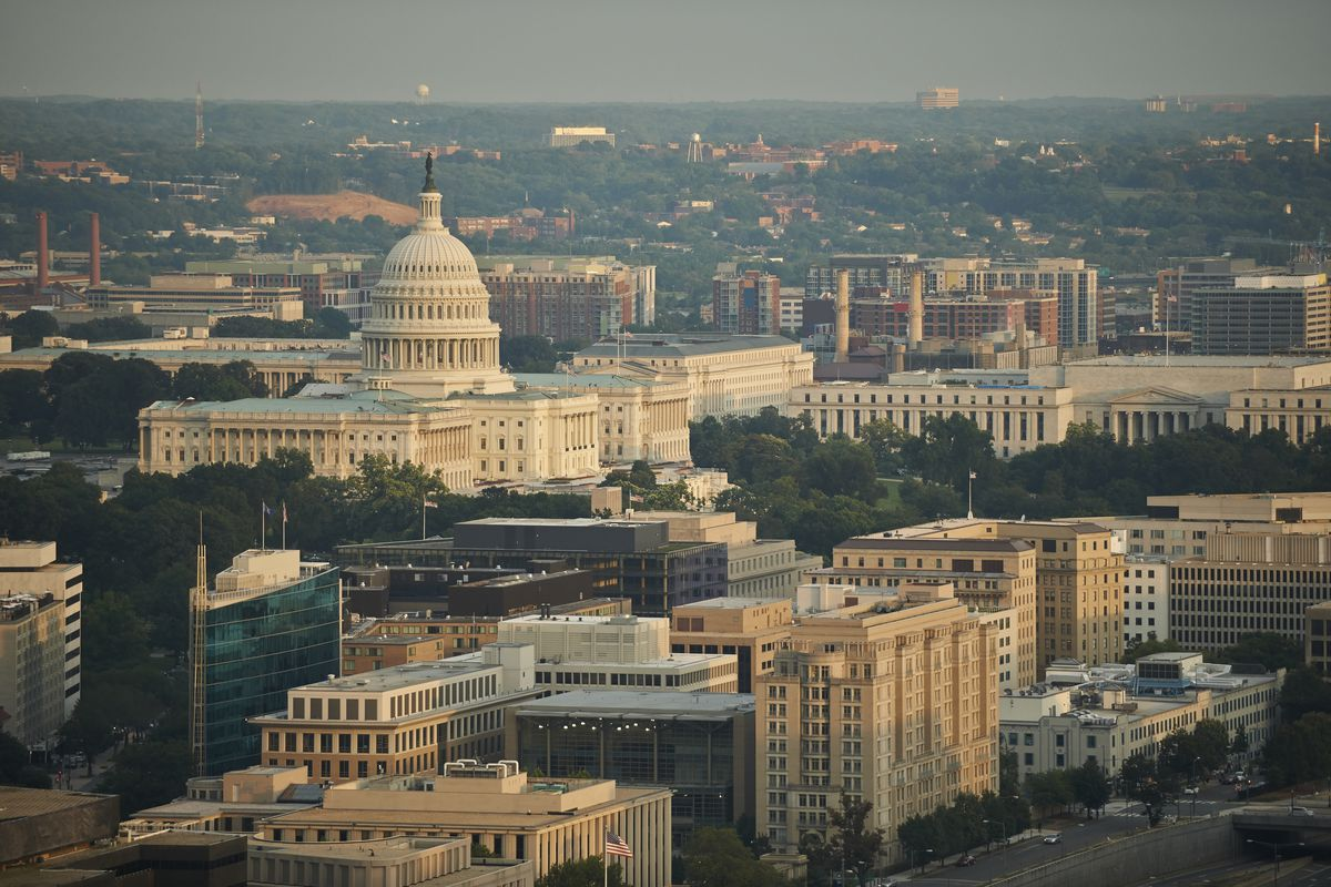 A domed Capitol building surrounded by office buildings.