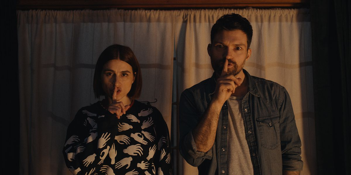 """Josh Ruben and Aya Cash stare into the camera and make the """"shhh"""" gesture in Scare Me"""