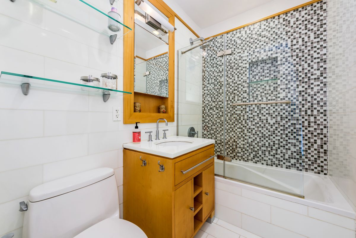 A bathroom with white tiles and a mosaic wall in its shower.