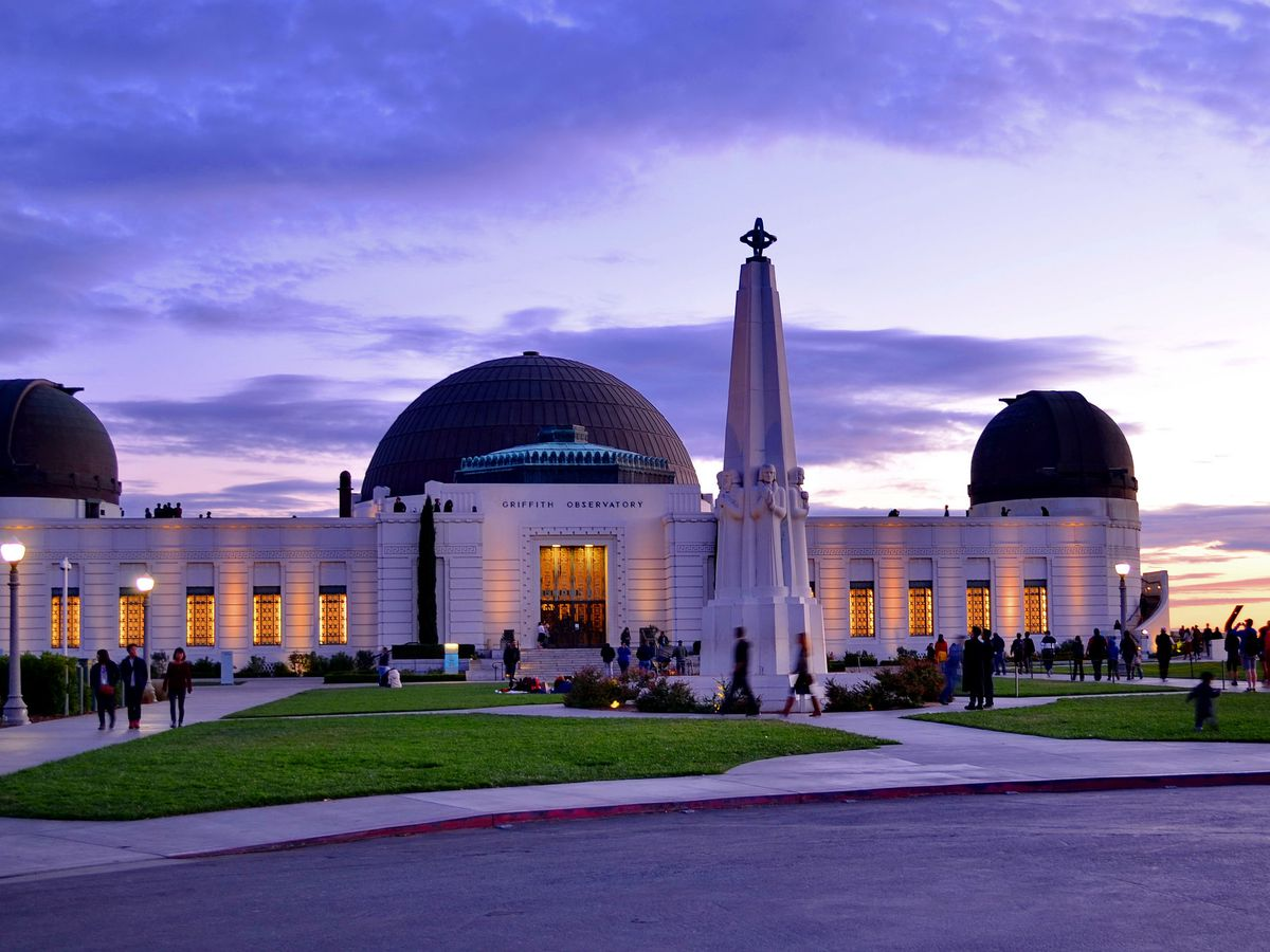 A white building with three domed towers. There is a lawn in front of the building and a pedestrian plaza. It is sunset and the sky is purple and orange.