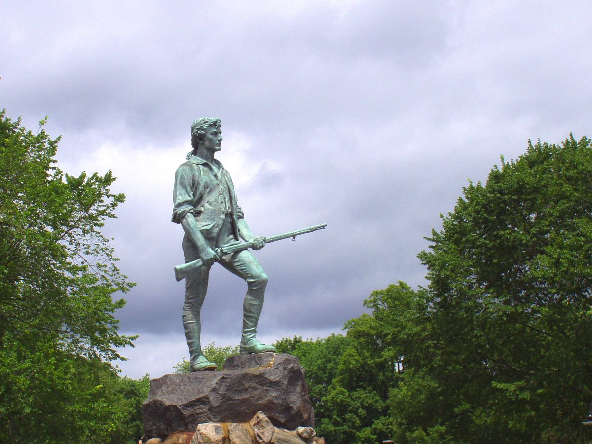 A bronze statue of a man with a rifle.