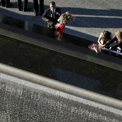 A man paces a bouquet of flowers at a reflecting pool during a ceremony at the National September 11 Memorial, Tuesday, Sept. 11, 2012 in New York.   As in past years, thousands are expected to gather at the World Trade Center site in New York, the Pentagon and Shanksville, Pennsylvania, to read the names of nearly 3,000 victims killed in the worst terror attack in U.S. history.