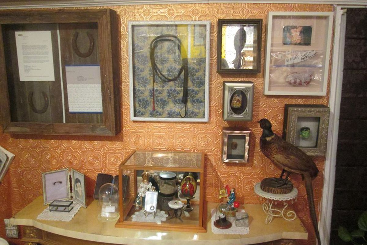 A collection of oddities displayed on a table and a wall