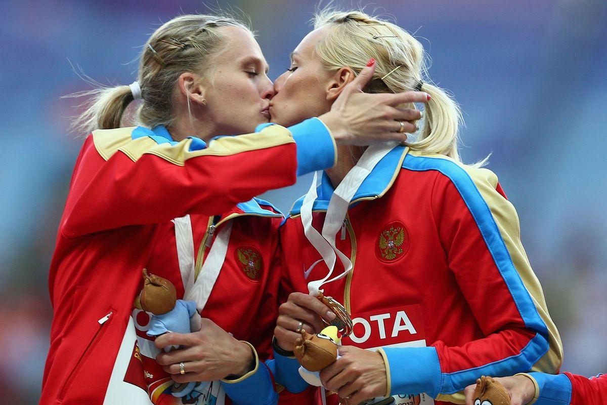 Tatyana Firova, left, and Kseniya Ryzhova of Russia kiss on the podium.