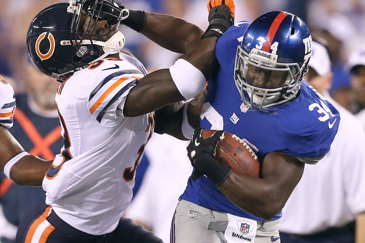 EAST RUTHERFORD, NJ - AUGUST 24:  David Wilson #34 of the New York Giants is shoves by Charles Tillman #33 of the Chicago Bears during a preseason game on August 24, 2012 at MetLife Stadium in East Rutherford, New Jersey. (Photo by Elsa/Getty Images)