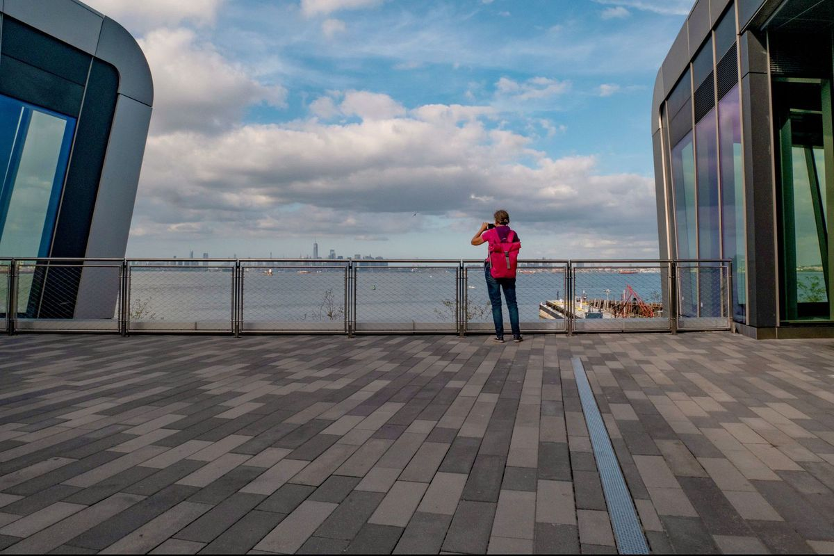 A woman wearing a red backpack stands on an outdoor patio overlooking a large river. She is taking a picture of tall buildings in the distance.