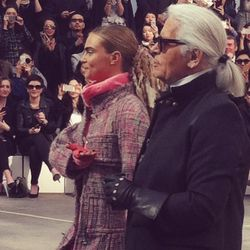 Karl takes his bow with <b>Cara Delevingn</b>e. She looks very tan. I love the hair throughout the whole show—it's sort of <b>a high-end take on a dread-locked gutter punk style</b>, with a ponytail that has strips of fabric woven through it. I contemplat