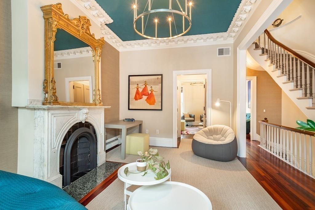 A narrow living room next to a hallway next to a stairwell, and there's a large marble fireplace in the living room.