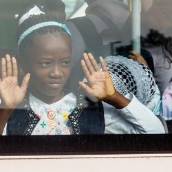 A young girl looks out of the window of a bus after being evacuated from Brussels airport, after explosions rocked the facility in Brussels, Belgium, Tuesday March 22, 2016. Authorities locked down the Belgian capital on Tuesday after explosions rocked the Brussels airport and subway system, killing at least 34 people and injuring many more. Belgium raised its terror alert to its highest level, diverting arriving planes and trains and ordering people to stay where they were. Airports across Europe tightened security.