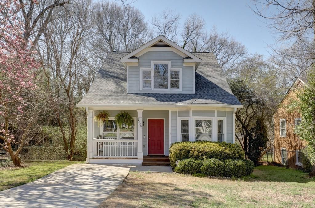 Light gray house with red door and covered porch