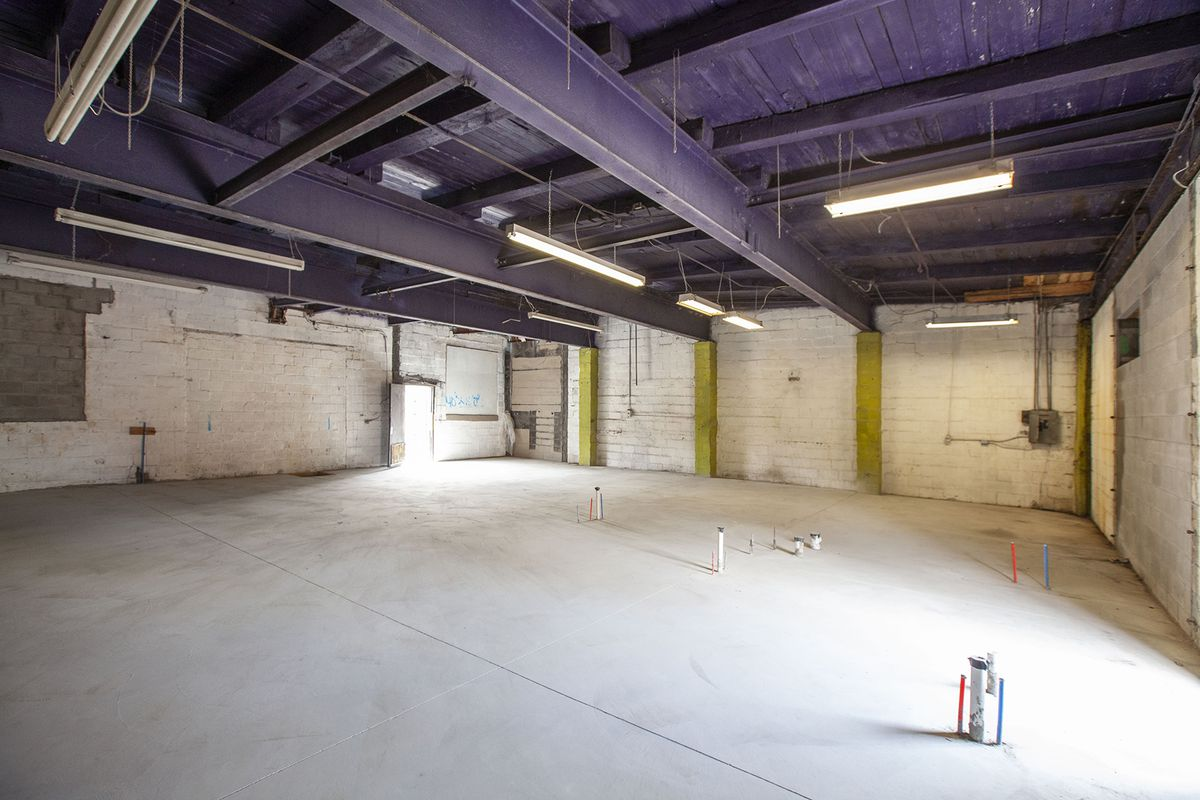 A big empty room with no windows and a purple-painted wood and steel beam ceiling.