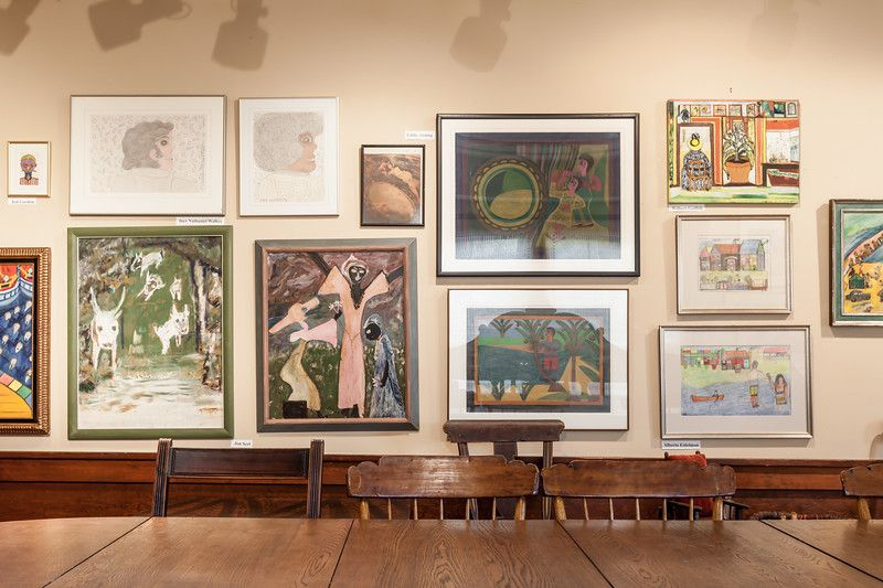 A wall with multiple framed works of art. In the foreground is a wooden table with chairs.