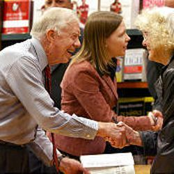 """Former President Jimmy Carter shakes hands with a fan during a book signing for """"Our Endangered Values: America's Moral Crisis"""" at Barnes \& Noble Tuesday in Salt Lake City."""