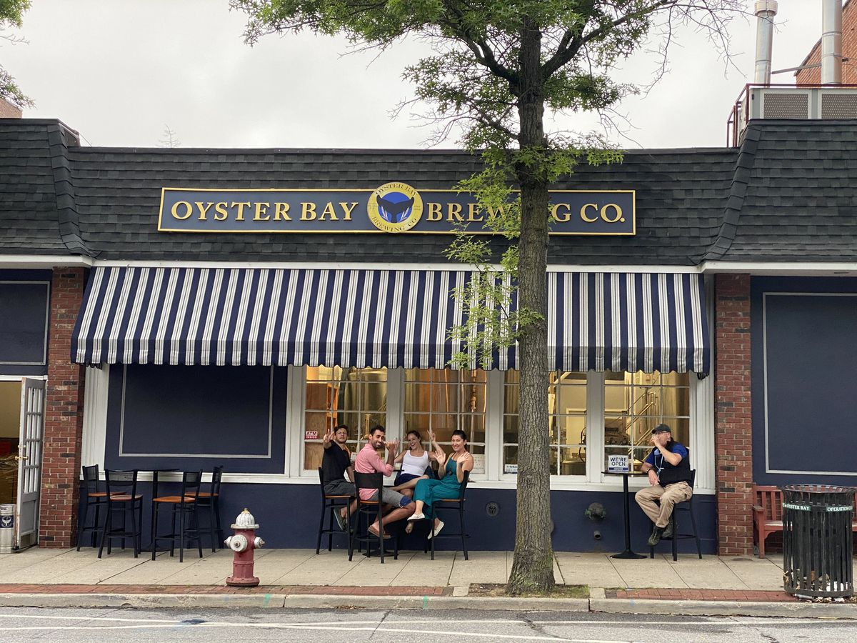Patrons on stools drink outside of Oyster Bay Brewing Co