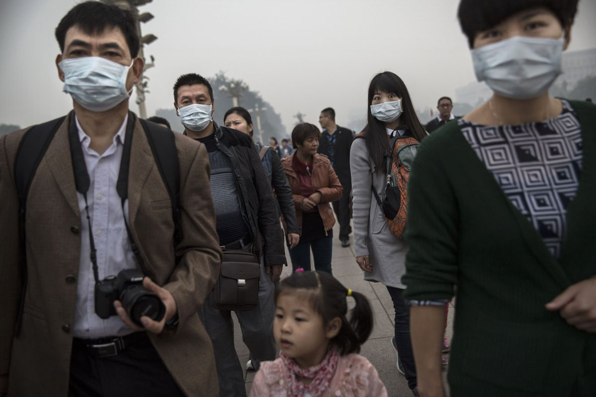 A family walks near Tiananmen Square on a smoggy day