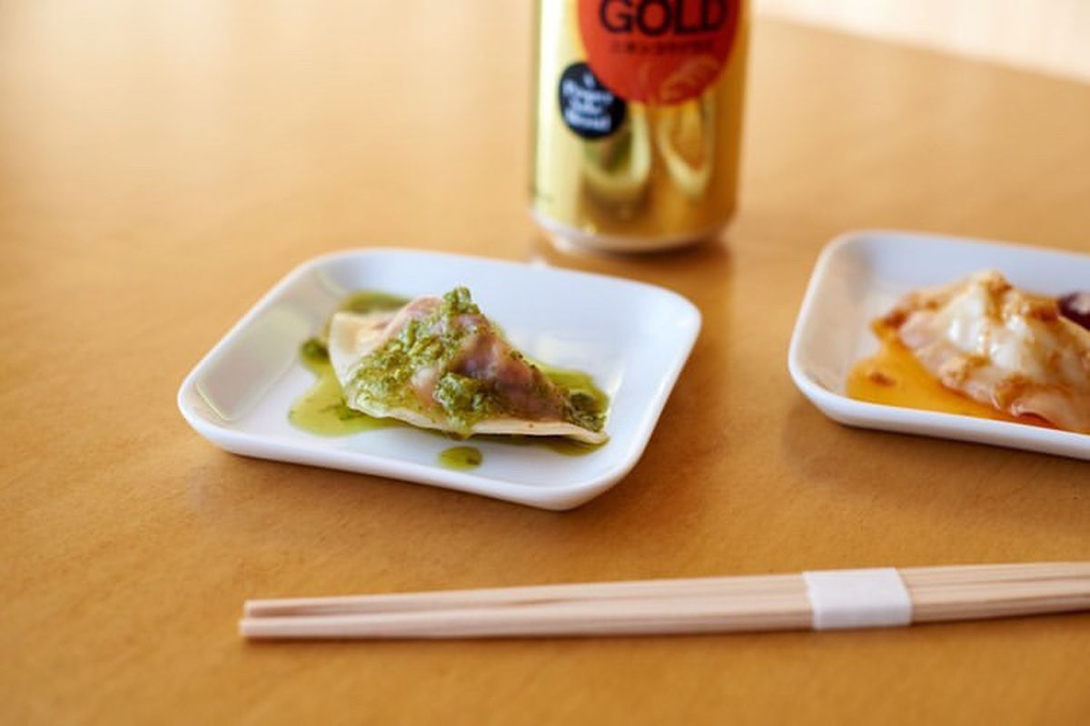 Two small, square white plates with sauce-topped steamed dumplings. There is a gold beer can in the background and there are chopsticks in the foreground.