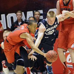 Utah Utes guard Brandon Taylor (11) and Brigham Young Cougars forward Eric Mika (00) fight for a loose ball as Mika has his arm grabbed by Utah Utes forward Renan Lenz (10) during a game at the Jon M. Huntsman Center on Saturday, Dec. 14, 2013.