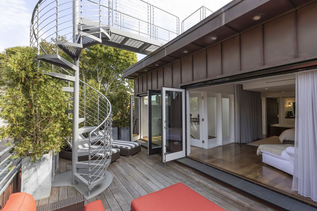 A bedroom has retractable doors that open to a rooftop patio with a spiral staircase and trees.