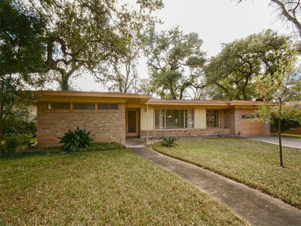 low-slung 1953 modern home with flat roof, beige brick pattern, clerestory and picture windows