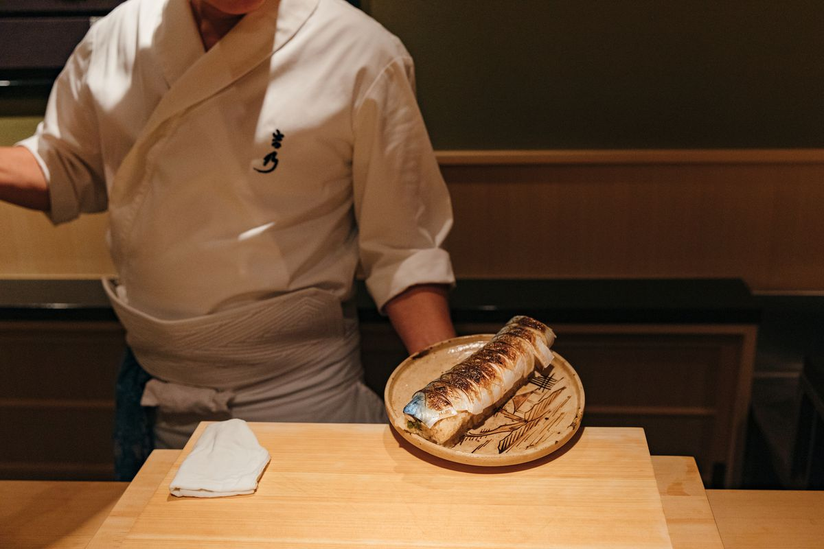 A chef in a white a uniform presents a plate of seated mackerel on rice.