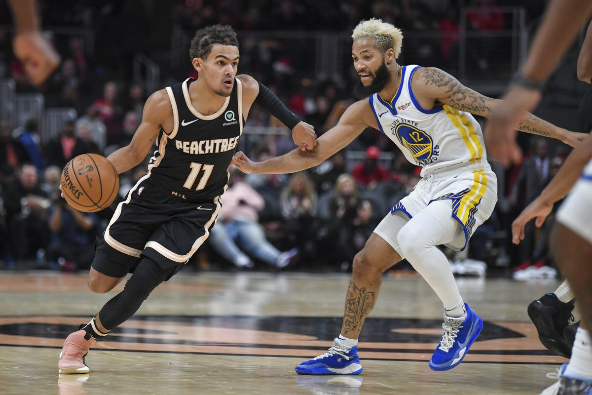 Atlanta Hawks guard Trae Young drives past Golden State Warriors guard Ky Bowman during the second half at State Farm Arena.