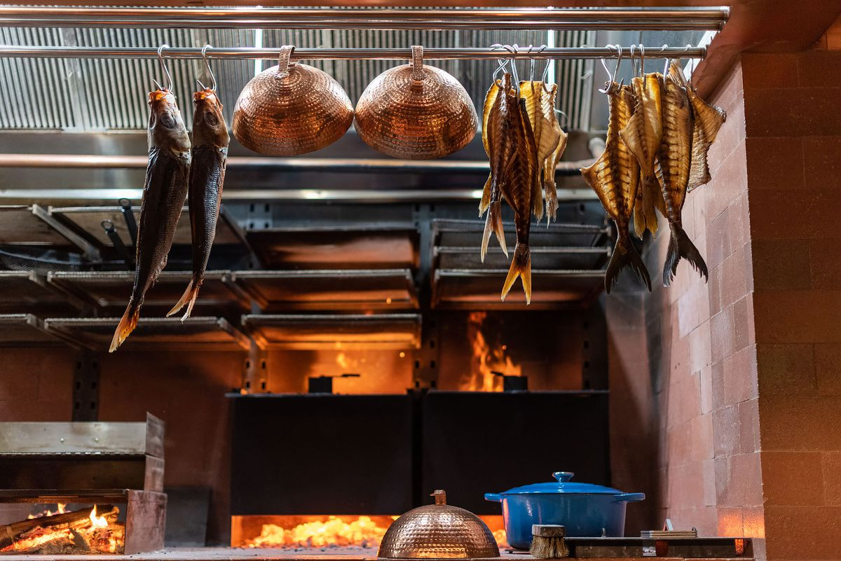 An open fire grill shows hanging seafood on metal racks.