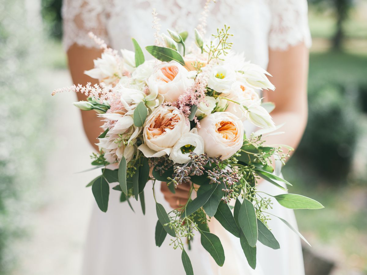 A woman in a wedding dress holds a bouquet with peonies in it.