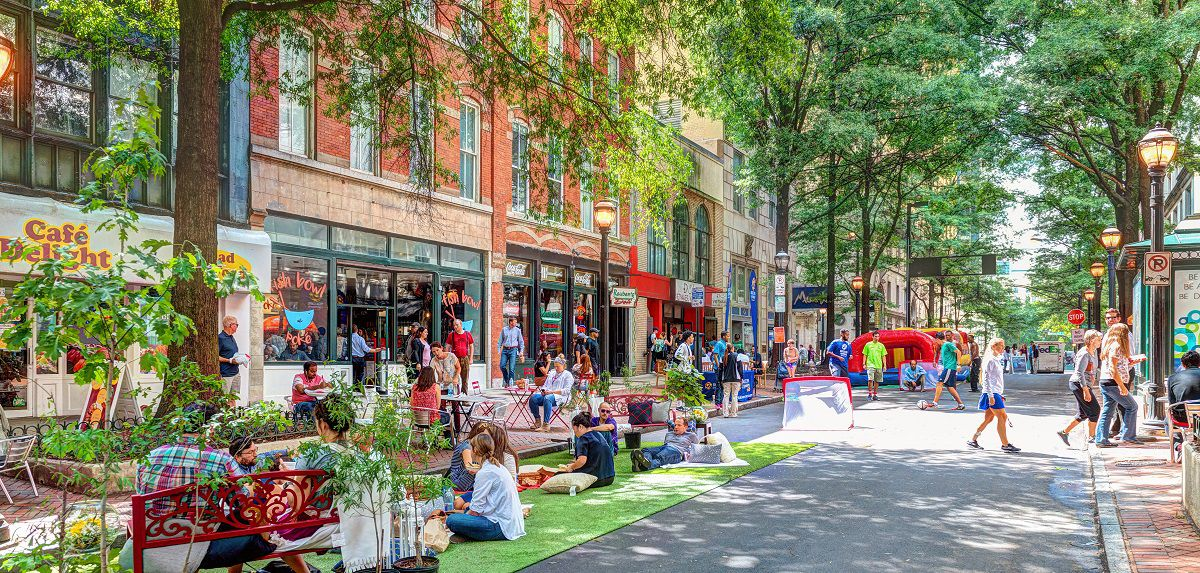 People sit and walk through the downtown's Broad street, which is lined with retail buildings and greenery.
