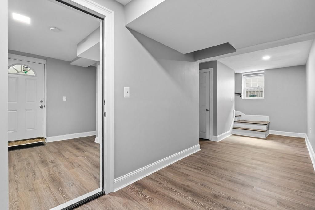 The lower, empty level of a duplex, with a hallway leading to a front room—also empty.