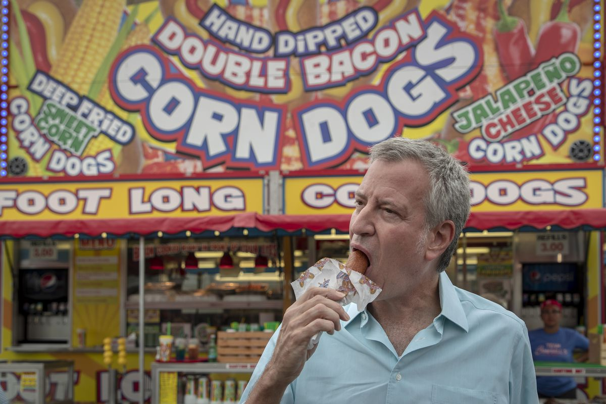 "de Blasio in front of a stand with a large ""Hand Dipped Double Bacon Corn Dogs"" sign, taking a large bite from a corn dog."