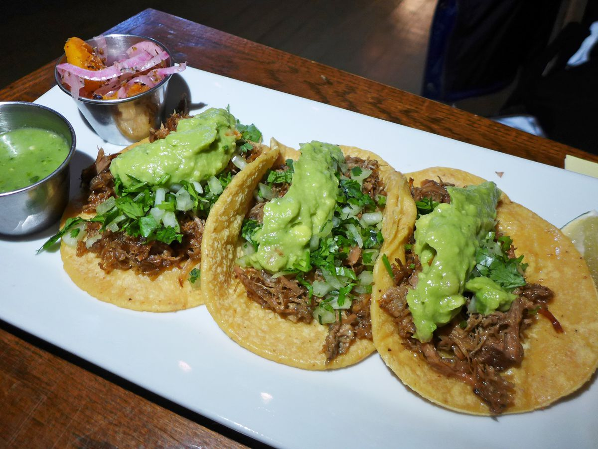 Three tacos of shredded meat topped with guacamole.