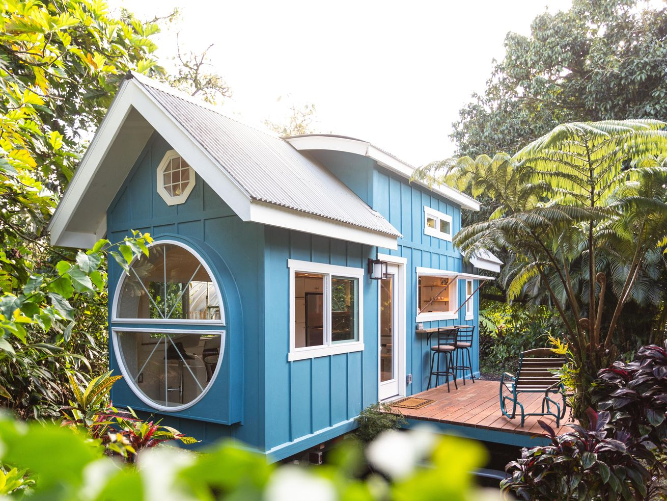 Blue tiny house with round windows at one end.