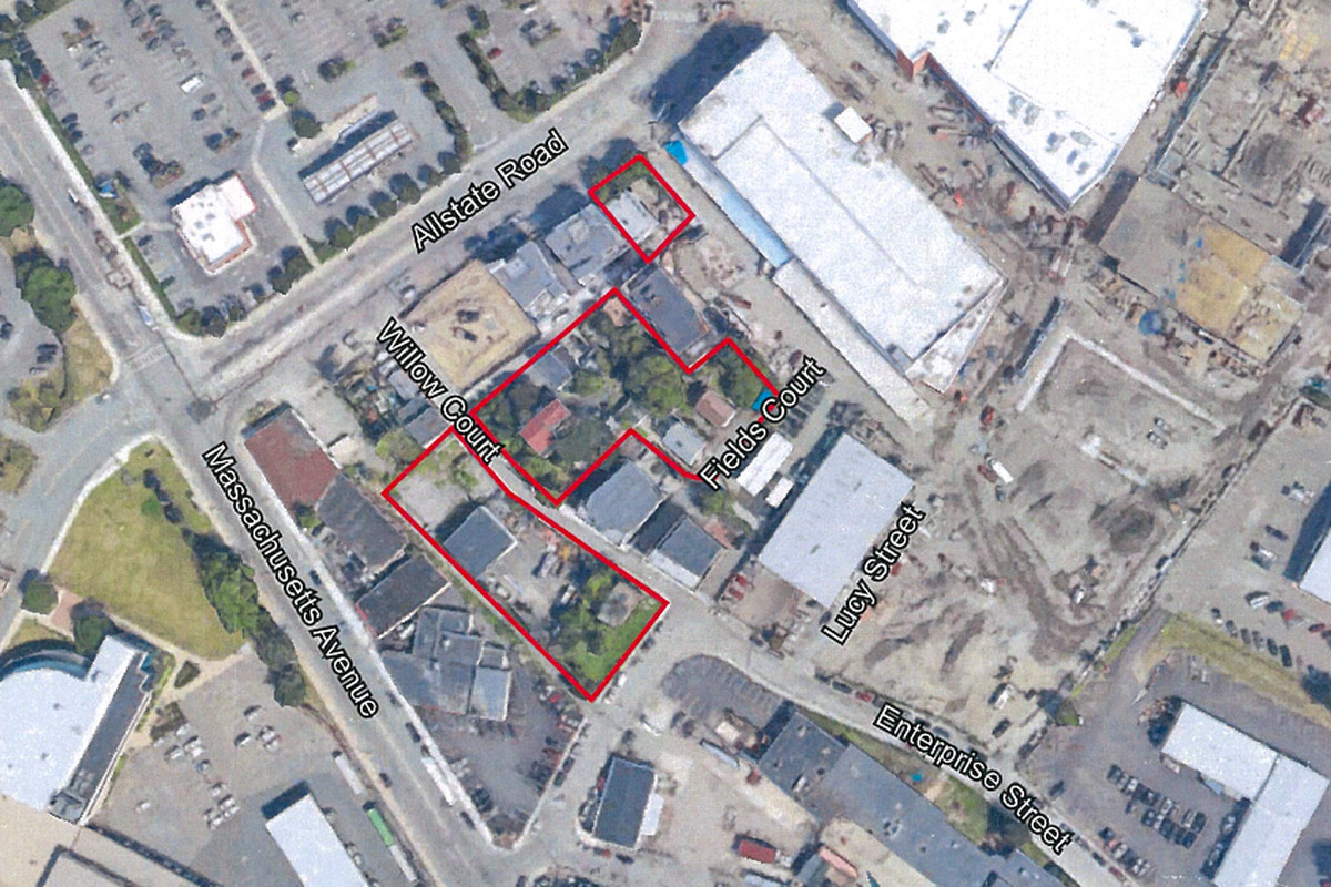 Aerial view of a street grid of a section of a city, with a red outline around a parcel slated for redevelopment.