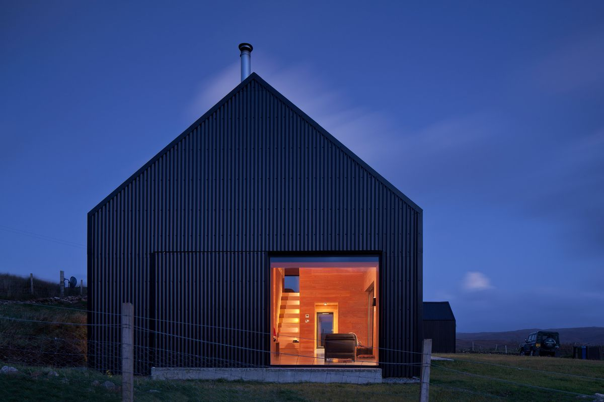 House at dusk with large glowing window